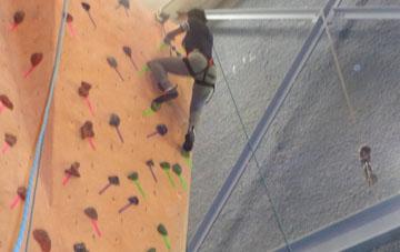 black woman rock climbing
